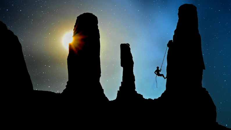 Man climbing mountain as sun sets behind a rock pillar.