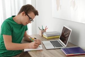High school student studying at home with a laptop and notebook