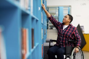 Student in a wheelchair reaching for a book in a library