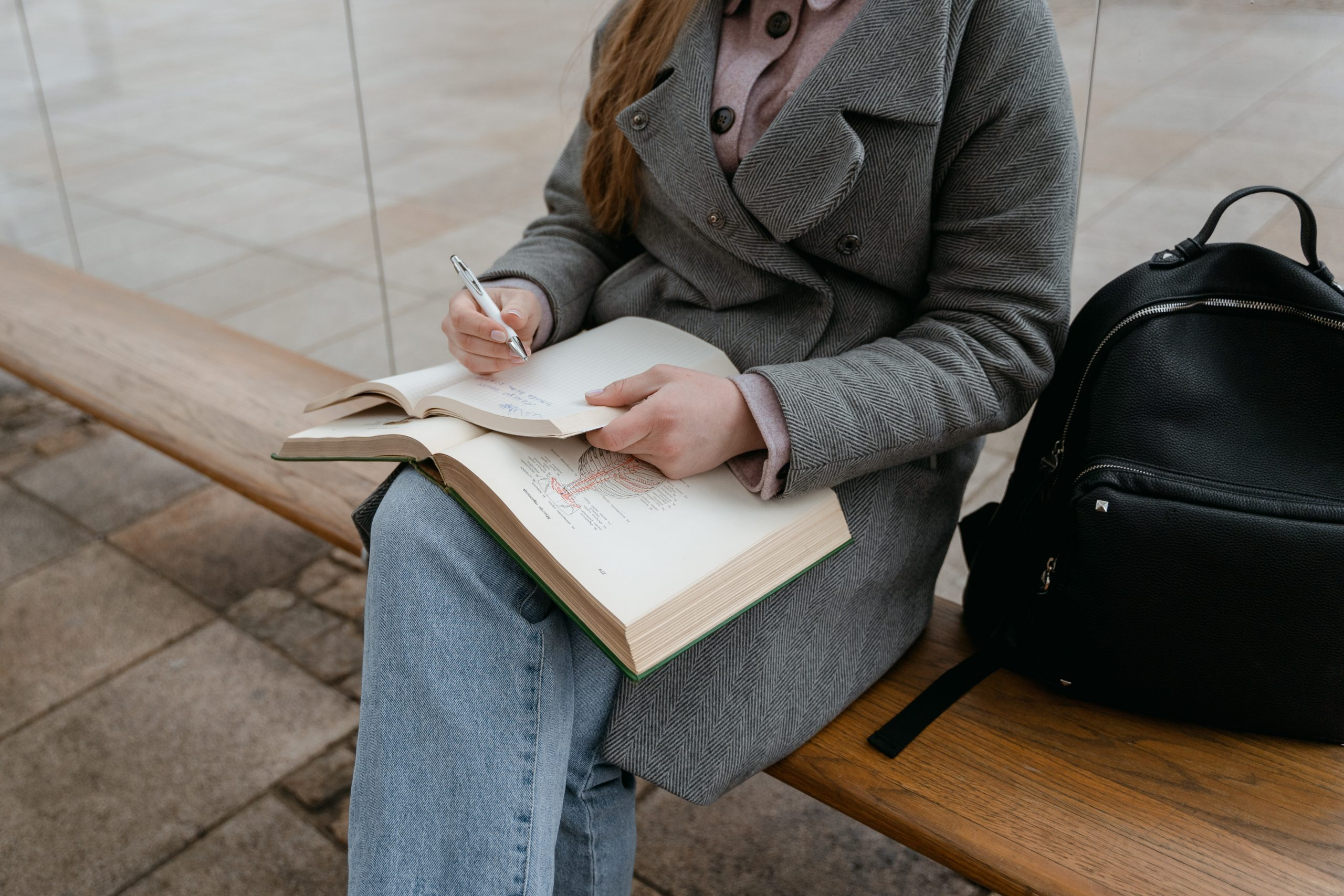 College student sitting on a bench reflecting on a reading assignment