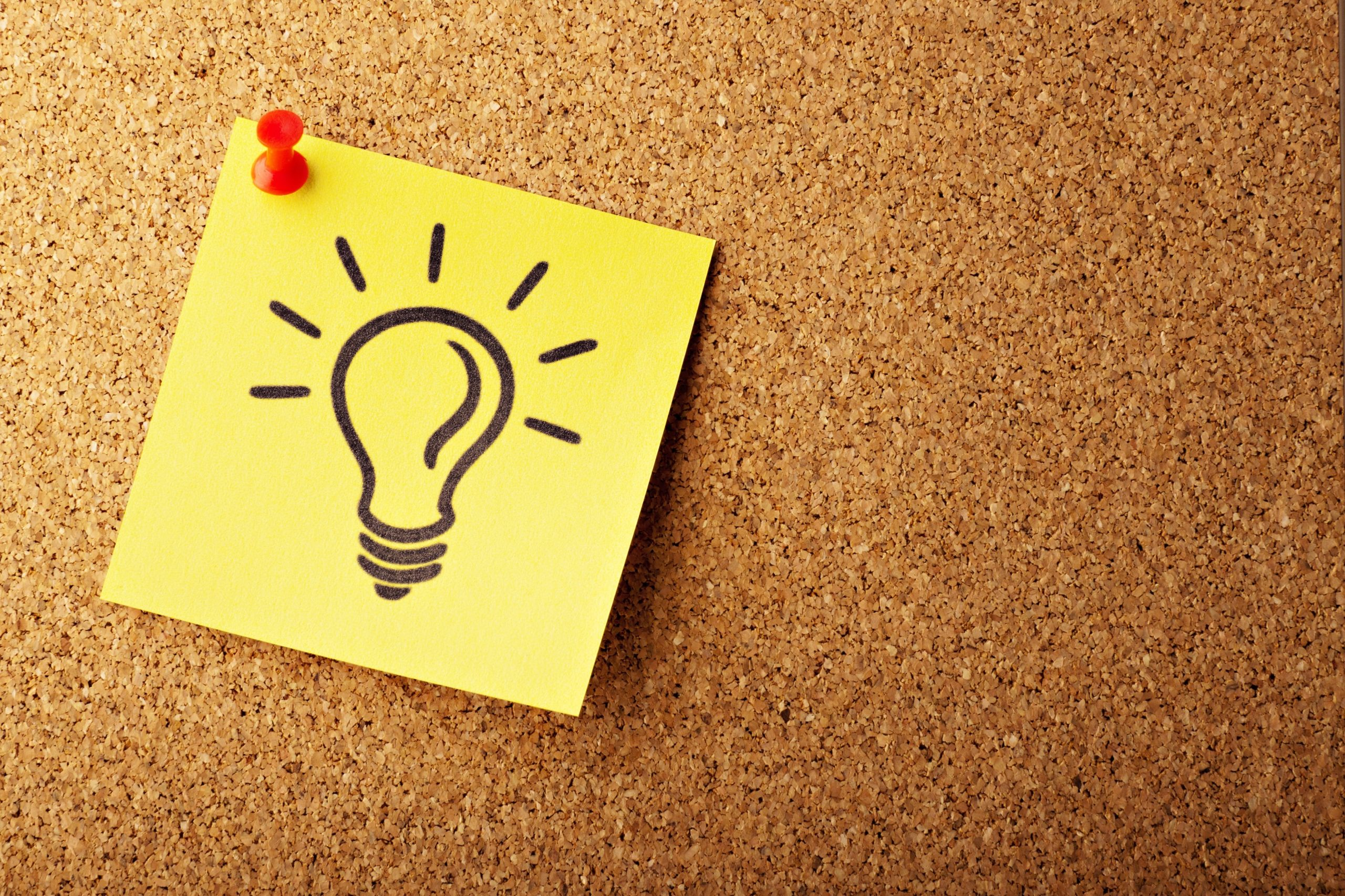 Yellow post-it note with a light bulb drawn on it, and pinned to a cork board