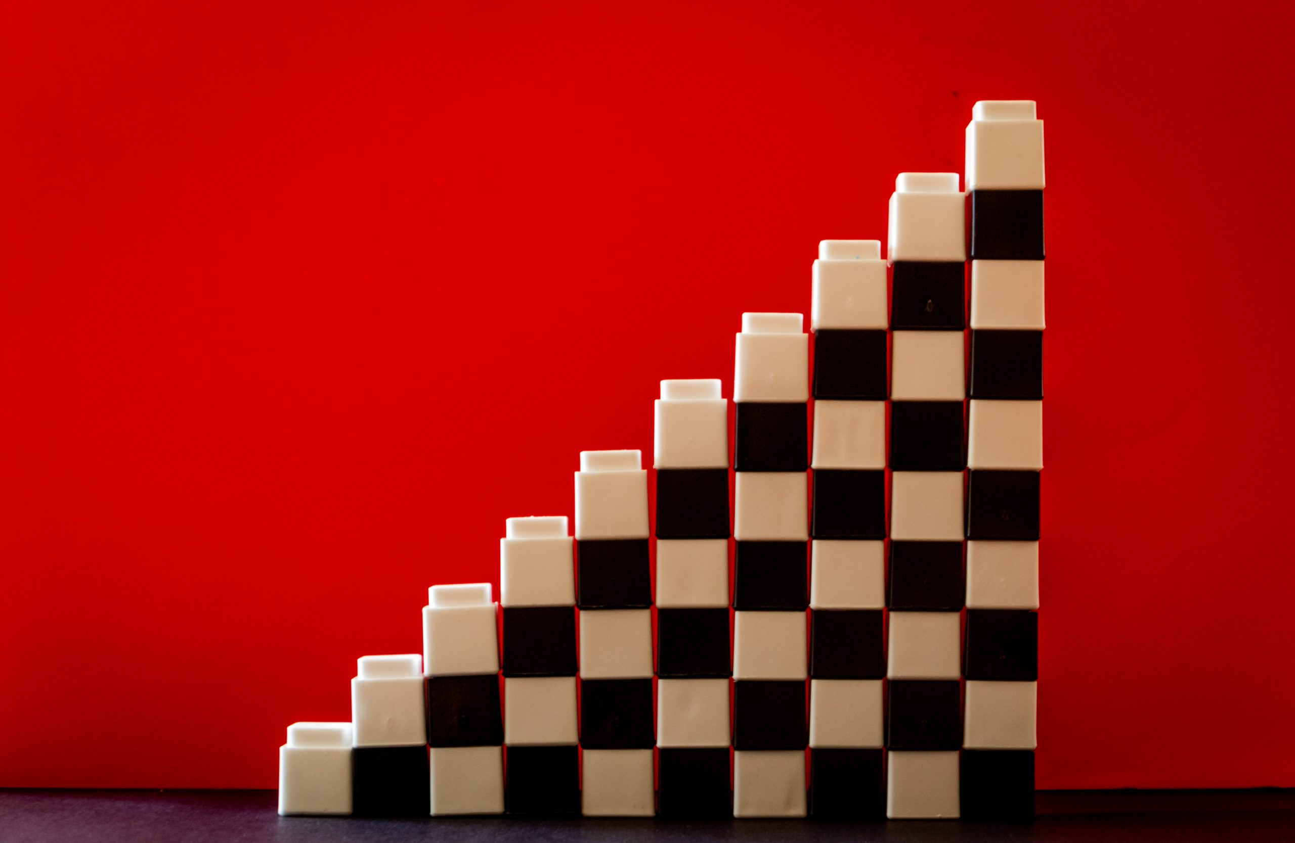 Stacked white and black blocks on a red background