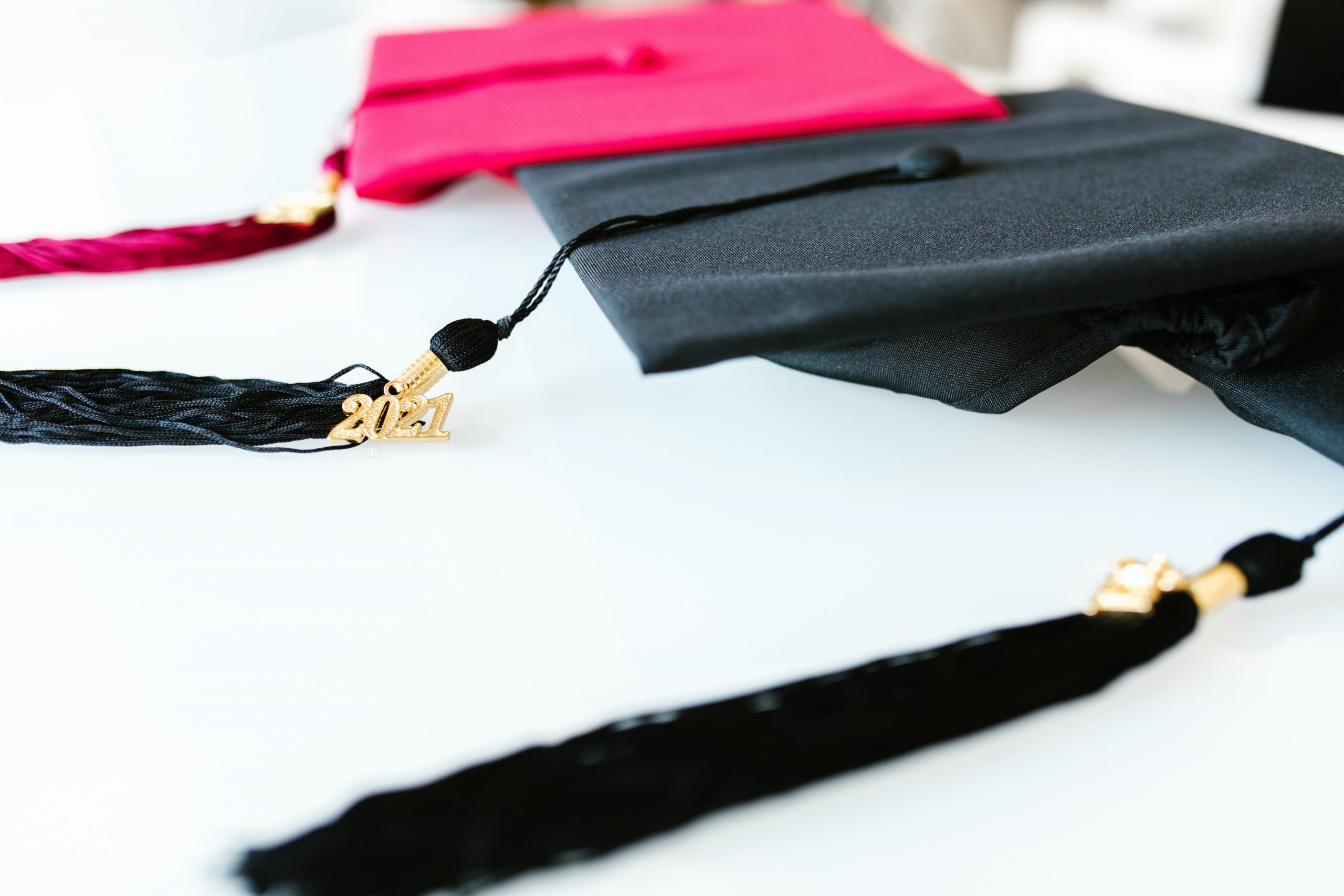 Red and black graduation caps and tassels on a white table